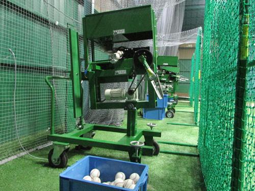 ボールパークでフル稼働している通常サイズのアーム式ピッチングマシン